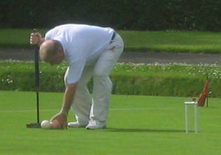 Joe Lennon places the pink for a croquet stroke
